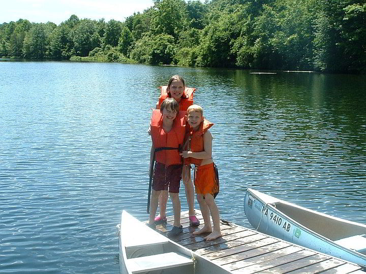 kids wearing life jackets while standing on dock